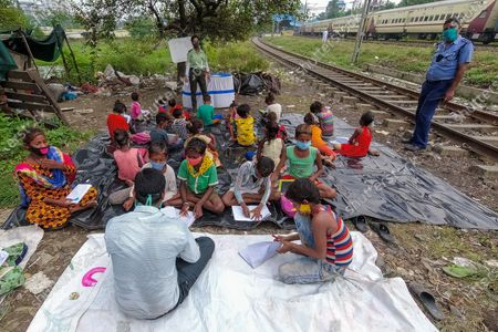 A lady volunteer of South West traffic guard teaching basic alphabets and numbering to chuildrens of a slum ,beside a railway track in Kolkata , India , on 13 August 2021 .A special class was organized by South west traffic guard to students belonging from slums of south Kolkata who cannot avail online classes or tuitions as all schools remain shut due to the pandemic.