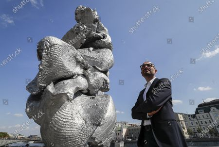 Francesco Manacorda, Artistic Director of the V-A-C Foundation, poses in front the sculpture 'Big clay No. 4' by Swiss artist Urs Fischer in Moscow, Russia, 16 August 2021. The 12-meter composition 'Big clay No. 4' cast from aluminium is a copy of a lump of clay that Urs Fischer was kneading in his hands. The sculpture will be on display for several months. Some residents of Moscow criticized the art object for being ugly.