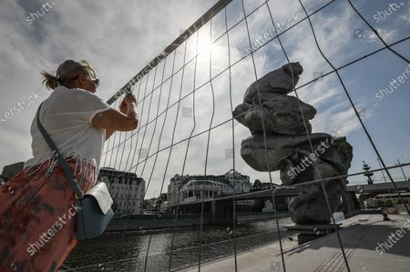 A woman takes a picture of the sculpture 'Big clay No. 4' by Swiss artist Urs Fischer in Moscow, Russia, 16 August 2021. The 12-meter composition 'Big clay No. 4' cast from aluminium is a copy of a lump of clay that Urs Fischer was kneading in his hands. The sculpture will be on display for several months. Some residents of Moscow criticized the art object for being ugly.