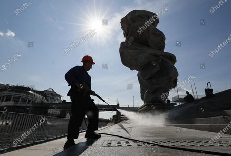 A streets cleaner works around the sculpture 'Big clay No. 4' by Swiss artist Urs Fischer in Moscow, Russia, 16 August 2021. The 12-meter composition 'Big clay No. 4' cast from aluminium is a copy of a lump of clay that Urs Fischer was kneading in his hands. The sculpture will be on display for several months. Some residents of Moscow criticized the art object for being ugly.
