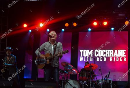 Canadian musician Tom Cochrane (center) and Bill Bell (left) perform on stage during Edmonton Rock Fest as part of the Together Again series at the historic Racetrack Infield on the Edmonton Exhibition Lands (formerly Northlands Park) in Edmonton.On Saturday, 14 August 2021, in Edmonton, Alberta, Canada.