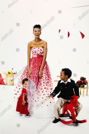 Ethiopian supermodel (and WHO -World Health Organization- Goodwill Ambassador for Maternal, Newborn and Child Health) Liya Kebede wearing a white tulle strapless dress with red polka-dot appliqué and red leather belt by Oscar de la Renta; posing with her two children: Suhul (age 6) and Raee (one); Suhul is seated on a red rocking horse and wears a white collared shirt navy blue sweater and khaki trousers; Raee is playing in the diaphanous folds of her mother's dress (Raee wears a red velvet baby dress with dark leggings/tights and silver shoes); on a white set with a few minimalist children's' toys in background.