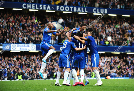 Alex Rodrigo Dias da Costa is mobed by delighted Chelsea team mates after scoring the second goal
