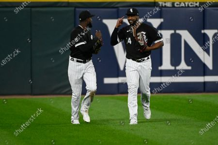 Chicago White Sox center fielder Luis Robert, left, and left fielder Eloy Jimenez (74) after Robert caught a ball hit by Oakland Athletics Seth Brown during the sixth inning of a baseball game, in Chicago