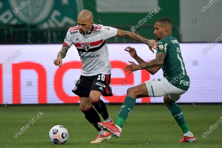 Wesley of Brazil's Palmeiras, right, and Daniel Alves of Brazil's Sao Paulo battle for the ball during a Copa Libertadores soccer match in Sao Paulo, Brazil