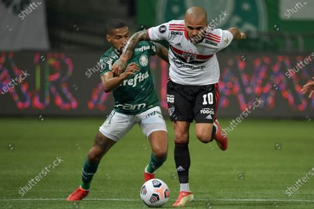 Wesley of Brazil's Palmeiras, left, and Daniel Alves of Brazil's Sao Paulo battle for the ball during a Copa Libertadores soccer match in Sao Paulo, Brazil