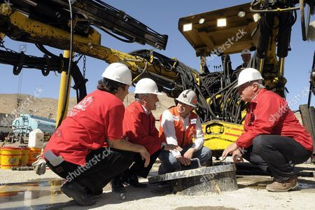 Chilean President Sebastian Pinera (2nd L) talking with mining minister Laurence Golborne (L), chief of the rescue mission Andre Sougarret (R), and health minister Jaime Manalich as they crouch over the cover to the shaft through which the trapped miners will be hoisted out at the San Jose copper mine.