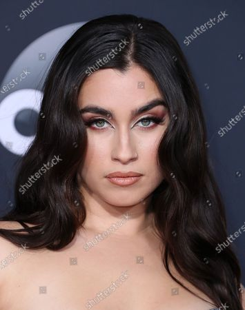 Singer Lauren Jauregui wearing an Usama Ishtay dress, Stuart Weitzman shoes, a Stefere hand cuff, and Kyle Chan earrings and bracelet arrives at the 2019 American Music Awards held at Microsoft Theatre L.A. Live on November 24, 2019 in Los Angeles, California, United States.