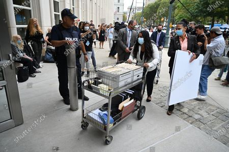 People arrive at the trial of Robert Sylvester Kelly, accused of sex trafficking and racketeering, at Brooklyn's federal court in New York.
