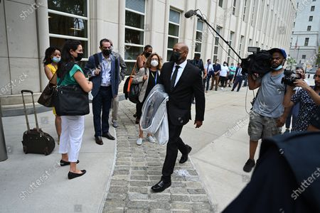 A man carries a suit for R Kelly to wear at the trial of Robert Sylvester Kelly, accused of sex trafficking and racketeering, at Brooklyn's federal court in New York.