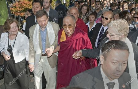 The Dalai Lama leaves for lunch with Eckhart Tilley (L) and Sir Ken Robinson (R) from the 2009 Vancouver Peace Summit at the University of British Columbia's Chan Centre in Vancouver, British Columbia, September 27, 2009.