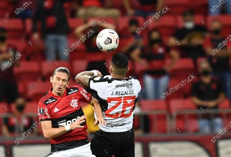 Filipe Luis of Brazil's Flamengo, left, and Jorge Recalde of Paraguay's Olimpia head for the ball during a Copa Libertadores soccer match at National Stadium in Brasilia, Brazil, Wednesday, Aug.18, 2021