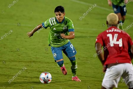 Seattle Sounders forward Raul Ruidiaz (9) dribbles the ball upfield as FC Dallas defender Nkosi Burgess (14) looks on in the second half during an MLS soccer match, in Frisco, Texas