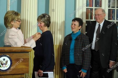 """Stock Image of Secretary of State Hillary Rodham Clinton gives Lynne Tracy with the Award for Heroism for her completion of a three year tour as principal officer at the U.S. Consulate in Peshawar, Pakistan, at the State Department in Washington on December 7, 2009. """"On August 26, 2008 gunmen ambushed her vehicle, riddling the car with bullets. Despite this, she remained in Peshawar for another year after the attack and continued to pursue U.S. policy at this critical post."""" At right are Tracy's parents Carol and Albert."""