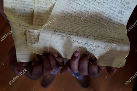 Michael Williams hold letters he wrote to his wife, Jacqueline Anderson, while incarcerated at the Cook County Jail, in his South Side Chicago home on