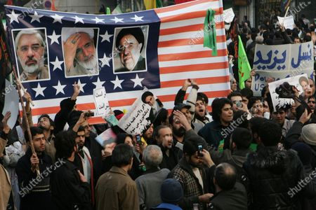 Iranian demonstrators display images of Iran's opposition leaders ,Mir-Hossein Mousavi (L) ,Mehdi Karroubi (M) and Mohammad Khatami (R) on an American flag during pro-government rallies in Tehran, Iran on December 30, 2009. Hundreds of thousands of supporters of Iranian President Mahmoud Ahmadinejad staged state-sponsored demonstrations throughout the country against the opposition.