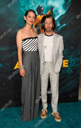"""Marion Cotillard, left, and Simon Helberg, cast members in """"Annette,"""" pose together at a special screening of the film at the Hollywood Forever Cemetery, in Los Angeles"""