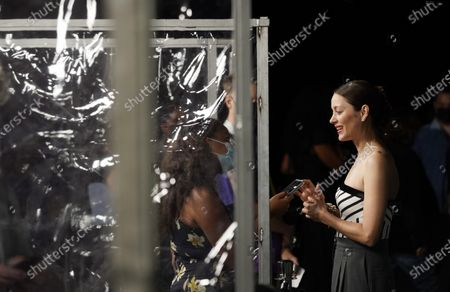 """Marion Cotillard, a cast member in """"Annette,"""" is interviewed by media behind dividers at a special screening of the film at the Hollywood Forever Cemetery, in Los Angeles. The dividers were put up to keep members of the media socially distanced"""