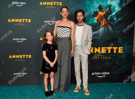 """From left, Devyn McDowell, Marion Cotillard and Simon Helberg, cast members in """"Annette,"""" pose together at a special screening of the film at Hollywood Forever Cemetery, in Los Angeles"""
