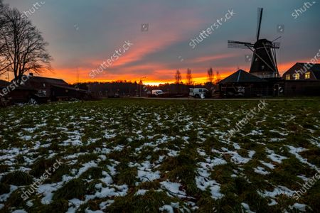 HDR - High Dynamic Range picture of a traditional Dutch windmill with snow on the grass as seen around sunset time at the sweet spot called magic hour at the dusk during a cold winter day, where the colorful clear sky is mixing with the clouds. The windmill,  a tourism attraction and symbol for the country, is located in the outskirts of Veldhoven, near the city of Eindhoven in North Brabant region. The specific mill is a bakery and cafe, the Oerse Mill Baker. Veldhoven, the Netherlands on January 25, 2021