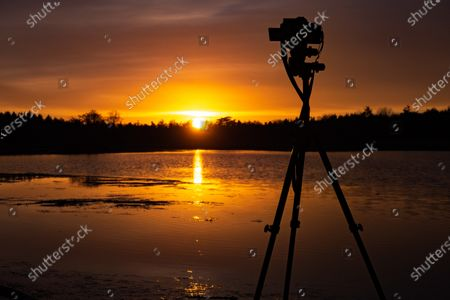 Silhouette of a camera on a tripod in action over the lake with the sun . Sunset time at the orange sky magic hour before the dusk, where the colorful clear sky is mixing with the clouds.  the Dutch countryside in Grootmeer en Kleinmeer lakes near Wintelre and Eindhoven airport during a cold winter day with frost. The fen and the water pond are a protected natural monument and part of the Kempenland-West Natura 2000 area preserving the environment and local wildlife. Wintelre - Vessem, Eersel, North Brabant, the Netherlands on January 25, 2021