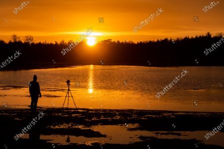 Silhouette of a photographer with a camera on a tripod in action over the lake. Sunset time at the orange sky magic hour before the dusk, where the colorful clear sky is mixing with the clouds.  the Dutch countryside in Grootmeer en Kleinmeer lakes near Wintelre and Eindhoven airport during a cold winter day with frost. The fen and the water pond are a protected natural monument and part of the Kempenland-West Natura 2000 area preserving the environment and local wildlife. Wintelre - Vessem, Eersel, North Brabant, the Netherlands on January 25, 2021