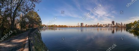 Jacqueline Kennedy Onassis water reservoir in Central Park, Manhattan in New York City. The Reservoir in NY covers 106 acres and holds over 1,000,000,000 US gallons (3,800,000 m3) of water.  The lake is popular for running, jogging, cycling or strolling around. A clear blue sky day with buildings of Central Park West reflecting in the water with the fountain and ducks in it.  NYC, USA