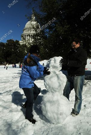 Megan and Luke Meier build a snowman near the U.S. Capitol building in Washington on February 14, 2010, after 2 snowstorms blanketed the city in record-setting snow totals. Washington received 55.9 inches of snow to date, the most snow the city has seen in one winter ever on record, and is expecting 1-4 more inches in the next 24 hours.