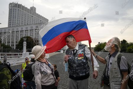 People who turned up to oppose a hard-line Soviet coup in August 1991, speak to each other as they gather with a Russian national flag to mark the 30th anniversary of the first day of the failed coup outside the Russian Government also known as White House building in Moscow, Russia, . The world held its breath 30 years ago when a group of top Communist officials ousted Soviet leader Mikhail Gorbachev and flooded Moscow with tanks. But instead of bringing a rollback of liberal reforms and a return to Cold War confrontations, the August 1991 coup collapsed in just three days and precipitated the breakup of the Soviet Union a few months later