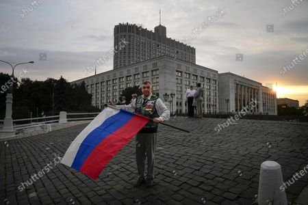 Stock Image of An elderly man, one of people who turned up to oppose a hard-line Soviet coup in August 1991, folds the Russian national flag after marking the 30th anniversary of the first day of the failed coup outside the Russian Government also known as White House building in Moscow, Russia, . The world held its breath 30 years ago when a group of top Communist officials ousted Soviet leader Mikhail Gorbachev and flooded Moscow with tanks. But instead of bringing a rollback of liberal reforms and a return to Cold War confrontations, the August 1991 coup collapsed in just three days and precipitated the breakup of the Soviet Union a few months later