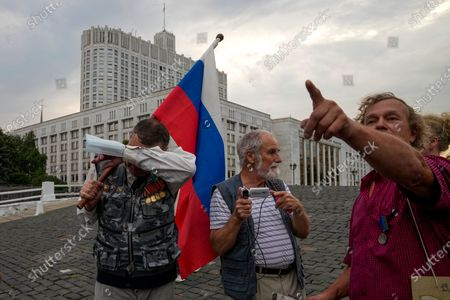 Stock Photo of One of people who turned up to oppose a hard-line Soviet coup in August 1991, reacts, as other speak to each other as they gather with a Russian national flag to mark the 30th anniversary of the first day of the failed coup outside the Russian Government also known as White House building in Moscow, Russia, . The world held its breath 30 years ago when a group of top Communist officials ousted Soviet leader Mikhail Gorbachev and flooded Moscow with tanks. But instead of bringing a rollback of liberal reforms and a return to Cold War confrontations, the August 1991 coup collapsed in just three days and precipitated the breakup of the Soviet Union a few months later