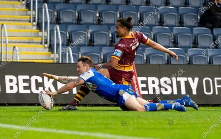 Huddersfield's Ashton Golding can't prevent Leeds's Richie Myler from scoring a try.