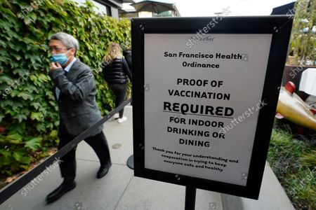 Diner makes his way into the Waterbar restaurant past a proof of vaccination sign, in San Francisco. Anyone who wants to eat, drink or exercise indoors in San Francisco must show they are fully vaccinated against COVID-19 when one of the nation's most stringent restrictions on unvaccinated people takes effect Friday