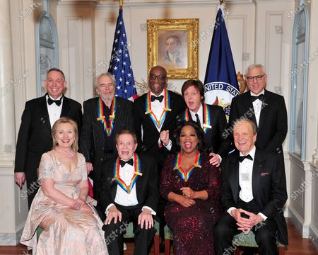 """The 2010 Kennedy Center honorees pose for their formal class photo following the formal Artist's Dinner at the United States Department of State in Washington, D.C. on Saturday, December 4, 2010.  Top row, from left to right: Michael M. Kaiser, President, John F. Kennedy Center for the Performing Arts; Merle Haggard; Bill T. Jones; Sir Paul McCartney; and David M. Rubenstein, Chairman, John F. Kennedy Center for the Performing Arts.  Bottom row, from left to right:  United States Secretary of State Hillary Rodham Clinton; Jerry Herman; Oprah Winfrey; and George Stevens, Jr., creator of """"The Kennedy Center Honors""""."""