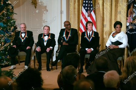 Kennedy Center Honorees listen to remarks by U.S. President Barack Obama as the president and First Lady Michelle Obama host the 2010 Kennedy Center Honorees at a reception in the East Room of the White House before going to the Kennedy Center on December 5, 2010.  The recipients for the 33rd annual awards are singer and songwriter Merle Haggard; composer and lyricist Jerry Herman; dancer, choreographer and director Bill T. Jones; songwriter and musician Paul McCartney; and producer, television host and actress Oprah Winfrey.