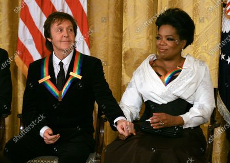 Paul McCartney holds the hand of Oprah Winfrey as they listen to remarks by U.S. President Barack Obama as the president and First Lady Michelle Obama host the 2010 Kennedy Center Honorees at a reception in the East Room of the White House before going to the Kennedy Center on December 5, 2010.  The recipients for the 33rd annual awards are singer and songwriter Merle Haggard; composer and lyricist Jerry Herman; dancer, choreographer and director Bill T. Jones; songwriter and musician Paul McCartney; and producer, television host and actress Oprah Winfrey.
