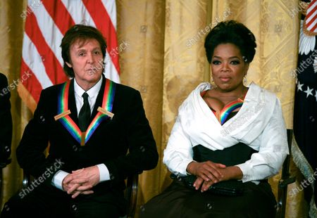 Paul McCartney and Oprah Winfrey listen to remarks by U.S. President Barack Obama as the president and First Lady Michelle Obama host the 2010 Kennedy Center Honorees at a reception in the East Room of the White House before going to the Kennedy Center on December 5, 2010.  The recipients for the 33rd annual awards are singer and songwriter Merle Haggard; composer and lyricist Jerry Herman; dancer, choreographer and director Bill T. Jones; songwriter and musician Paul McCartney; and producer, television host and actress Oprah Winfrey.