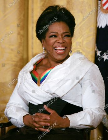 Oprah Winfrey smiles as she listens to remarks by U.S. President Barack Obama as the president and First Lady Michelle Obama host the 2010 Kennedy Center Honorees at a reception in the East Room of the White House before going to the Kennedy Center on December 5, 2010.  The recipients for the 33rd annual awards are singer and songwriter Merle Haggard; composer and lyricist Jerry Herman; dancer, choreographer and director Bill T. Jones; songwriter and musician Paul McCartney; and producer, television host and actress Oprah Winfrey.
