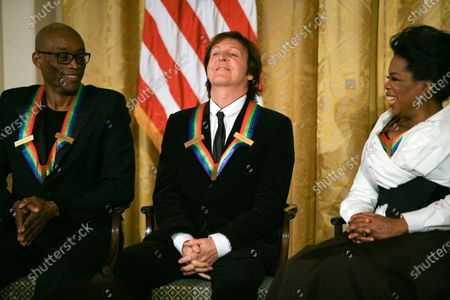 Paul McCartney reacts to commenst with Bill T. Jones (L) and Oprah Winfrey as they listen to remarks by U.S. President Barack Obama as the president and First Lady Michelle Obama host the 2010 Kennedy Center Honorees at a reception in the East Room of the White House before going to the Kennedy Center on December 5, 2010.  The recipients for the 33rd annual awards are singer and songwriter Merle Haggard; composer and lyricist Jerry Herman; dancer, choreographer and director Bill T. Jones; songwriter and musician Paul McCartney; and producer, television host and actress Oprah Winfrey.