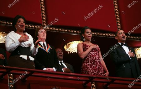 Stock Image of Oprah Winfrey (L) sing the National Anthem along with U.S. President Barack Obama First Lady Michelle Obama as Paul McCartney listens at the Kennedy Center on December 5, 2010. The recipients for the 33rd annual Kennedy Center honors are singer and songwriter Merle Haggard; composer and lyricist Jerry Herman; dancer, choreographer and director Bill T. Jones; songwriter and musician Paul McCartney; and producer, television host and actress Oprah Winfrey.