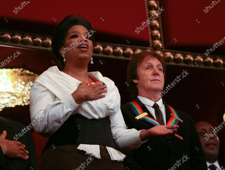 Oprah Winfrey (L) sing the National Anthem as Paul McCartney listens at the Kennedy Center on December 5, 2010. The recipients for the 33rd annual Kennedy Center honors are singer and songwriter Merle Haggard; composer and lyricist Jerry Herman; dancer, choreographer and director Bill T. Jones; songwriter and musician Paul McCartney; and producer, television host and actress Oprah Winfrey.