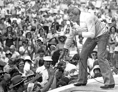 """Singer Tom T. Hall leans to the edge of the stage at the Jamboree in the Hills to meet the people near St. Clairsville, Ohio. Singer-songwriter Tom T. Hall, who composed """"Harper Valley P.T.A."""" and sang about life's simple joys as country music's consummate blue collar bard, has died. He was 85. His son, Dean Hall, confirmed the musician's death at his home in Franklin, Tennessee"""