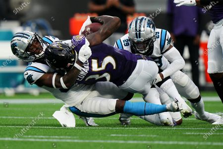 Baltimore Ravens running back Gus Edwards is tackled by Carolina Panthers defensive back Sean Chandler and cornerback Rashaan Melvin (29) during the first half of a preseason NFL football game, in Charlotte, N.C