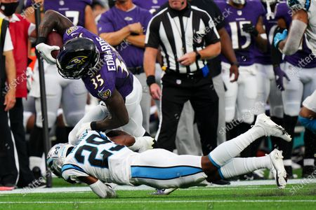 Baltimore Ravens running back Gus Edwards is tackled by Carolina Panthers cornerback Rashaan Melvin during the first half of a preseason NFL football game, in Charlotte, N.C
