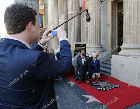 CBS news correspondent and New York Times best selling author Bill Geist (R) prepares to unveil his star while his son Willie Geist (L) records the event as he is honored with the 2,437th star on the Hollywood Walk of Fame in Los Angeles on April 15, 2011.