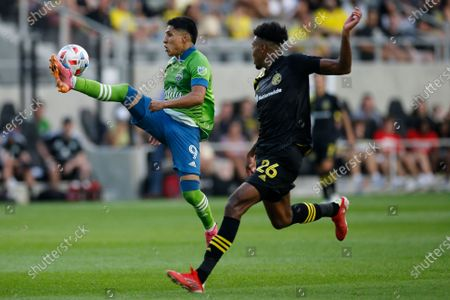 Seattle Sounders' Raul Ruidiaz, left, clears the ball away from Columbus Crew's Saad Abdul-Salaam during the second half of an MLS soccer match, in Columbus, Ohio