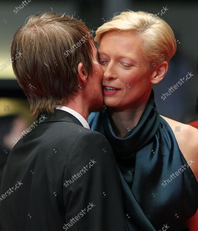 """Tilda Swinton (R) shares a kiss with Rory Stewart Kinnear on the red carpet before the screening of the film """"We Need to Talk About Kevin"""" during the 64th annual Cannes International Film Festival in Cannes, France on May 12, 2011."""