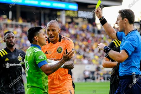 Raul Ruidiaz and Columbus Crew keeper Eloy Room interact as Ruidiaz is given a yellow card. Seattle Sounders defeated Columbus Crew at Lower.com Field in Columbus, Ohio one Aug. 21, 2021