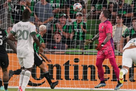 Austin FC's Diego Fagundez, left, puts a shot past Portland Timbers goalkeeper Steve Clark (12) for a goal during the first half of an MLS soccer match in Austin, Texas