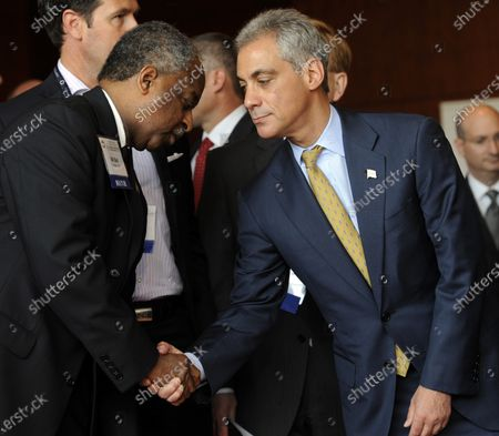 Chicago Mayor Rahm Immanuel greets Durham, North Carolina Mayor Bill Bell during an opening press conference for the 79th annual meeting of the United States Conference of Mayors in Baltimore on June 17, 2011.